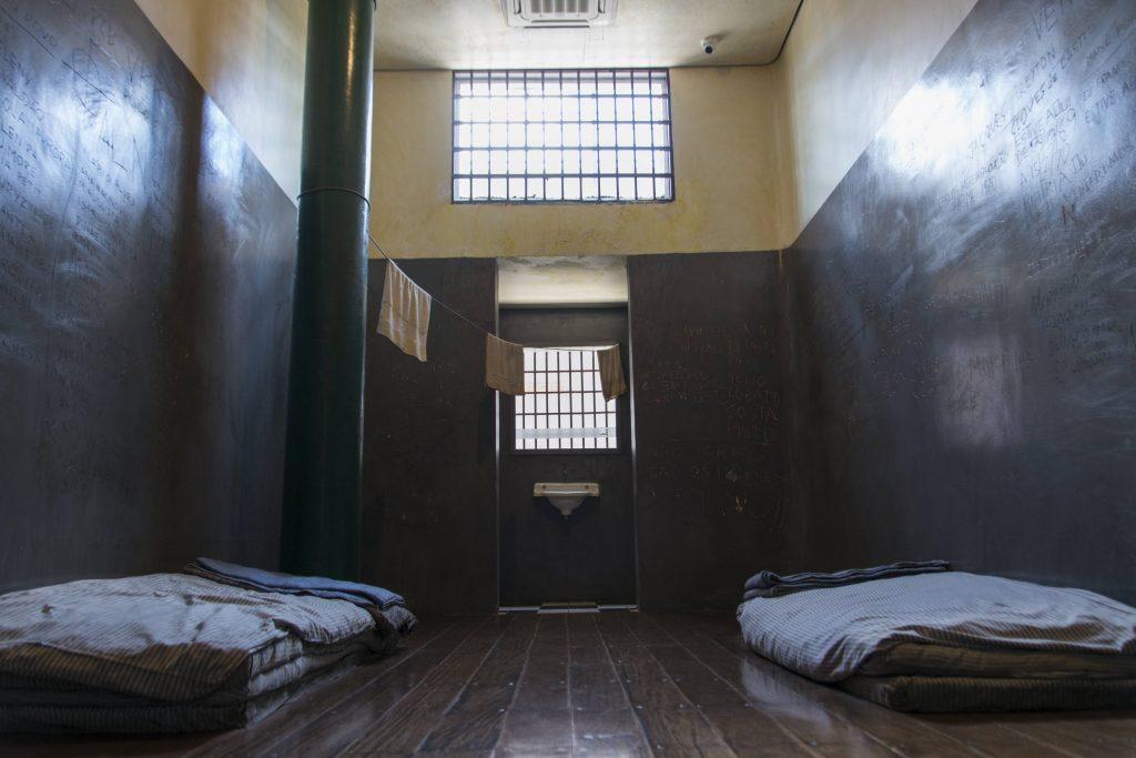 Foto colorida de cela com paredes cinza do chão até dois metros e de 2 metros para cima branca. O piso é de tábua corrida. Sobre o chão vemos colchonetes, do lado direito e esquerdo. No canto esquerdo da foto vemos uma pilastra verde. Ao fundo vemos uma entrada com pia branca.