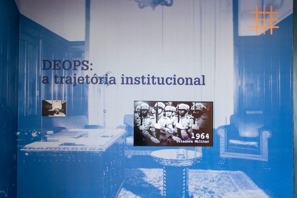 """Foto colorida de parede de espaço expositivo onde vemos uma aplicação de filtro azul em uma foto preto e branca plotada na parede com a imagem de um escritório com larga mesa entalhada, uma mesa de centro redonda em cima de um tapete persa, 2 poltronas e um sofá. Sobre a fotografia lemos os escritos """" Deops: a trajetória institucional"""". Em uma abertura no centro da parede vemos uma televisão que passa um vídeo com soldados armados e enfileirados e os escritos """"1964 - Ditadura Militar""""."""