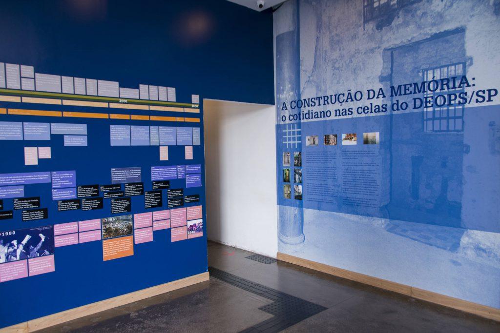 """Foto colorida de espaço expositivo com paredes azuis. Na parede da esquerda vemos o trecho final de uma linha do tempo com placas azuis, pretas e laranjas que contém fotos e informações escritas. Na parede da direita vemos uma aplicação de filtro azul em uma foto preto e branca plotada na parede com a imagem de uma cela em ruínas. Sobre a foto lemos os escritos """" A construção da memória: o cotidiano nas celas do Deops/SP"""", com letras azuis escuras."""