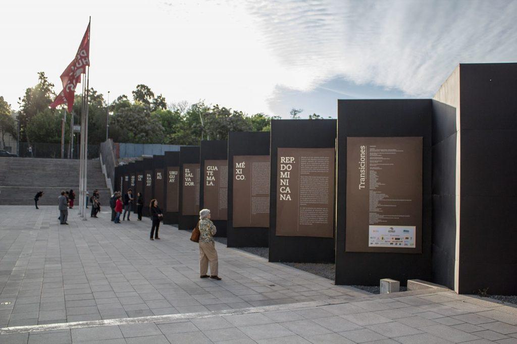 """Foto colorida de área externa de um museu com algumas pessoas vendo painéis. Eles são marrons com textos escritos em branco. Cada painel tem o nome de um país da América Latina. Na imagem podemos ler, da direita para esquerda, """"Republica Dominicana"""", """"México"""", """"Guatemala"""", """"El Salvador, """"Uruguay"""", """"Peru"""", """"Paraguay"""", """"Chile"""", """"Argentina"""" e """"Brasil"""". Ao fundo vemos bandeiras vermelhas e uma escadaria."""