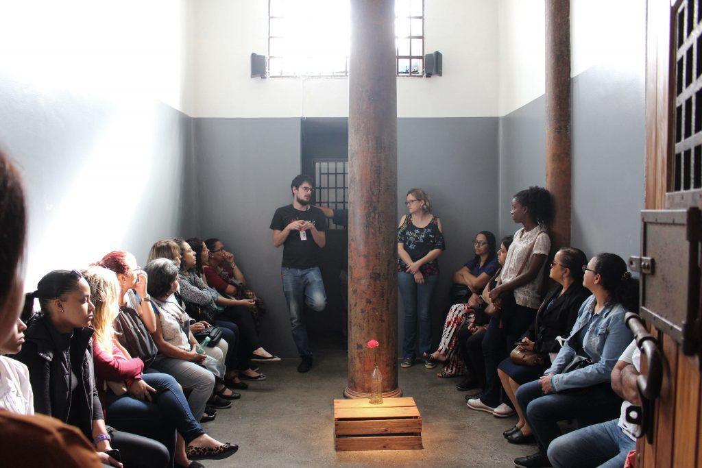 Foto de um grupo de mulheres sentadas nas laterais de uma cela, enquanto um educador fala. Elas olham para ele. No meio da foto vemos um caixote de madeira com um cravo vermelho dentro de uma embalagem de vinagre com água em frente a uma pilastra.
