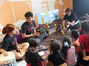 Foto de crianças assistindo a uma contação de história. Elas estão de costas para a foto e vemos duas educadoras e um educador manipulando carretéis de linha, um tambor e um painel de feltro com casas coloridas, uma árvore e um prédio.