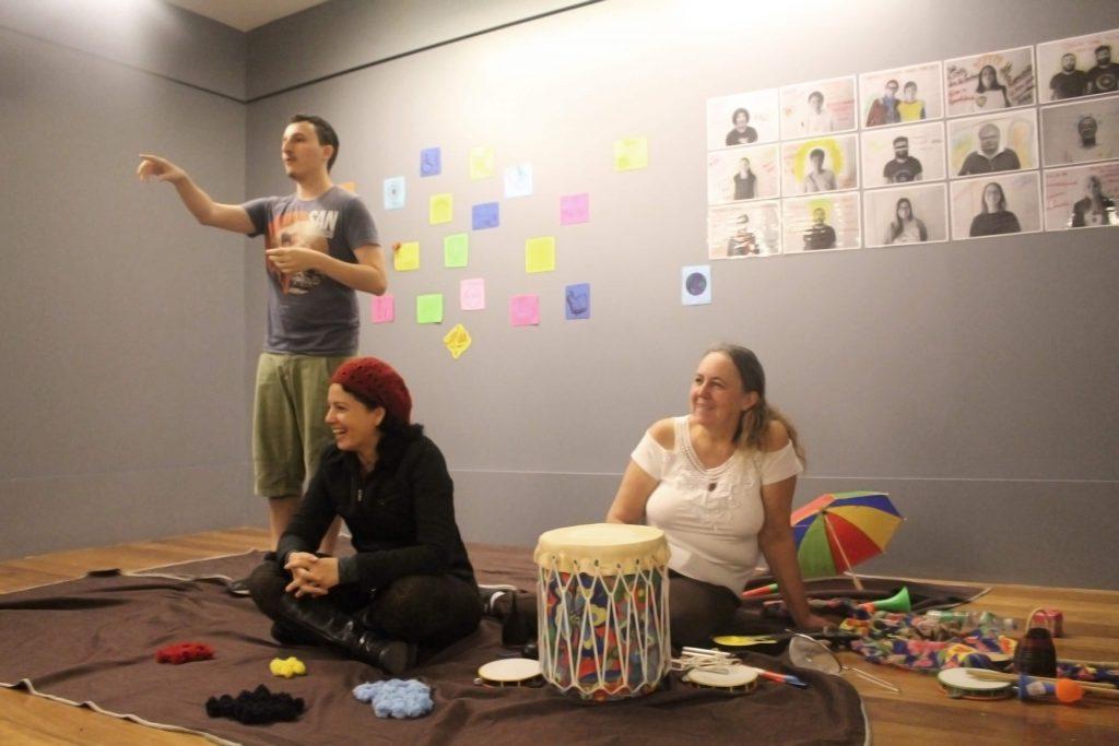 Foto de duas mulheres sentadas sobre um tecido marrom enquanto um homem em pé aponta para frente. Sobre o tecido também estão um tambor. Dois pandeiros, um guarda chuva de frevo e pompons pretos, azuis, amarelos e vermelhos.