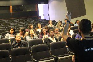Vemos em primeiro plano uma pessoa de costas segurando uma prancheta falando para um grupo de pessoas sentadas em um auditório que o observam.
