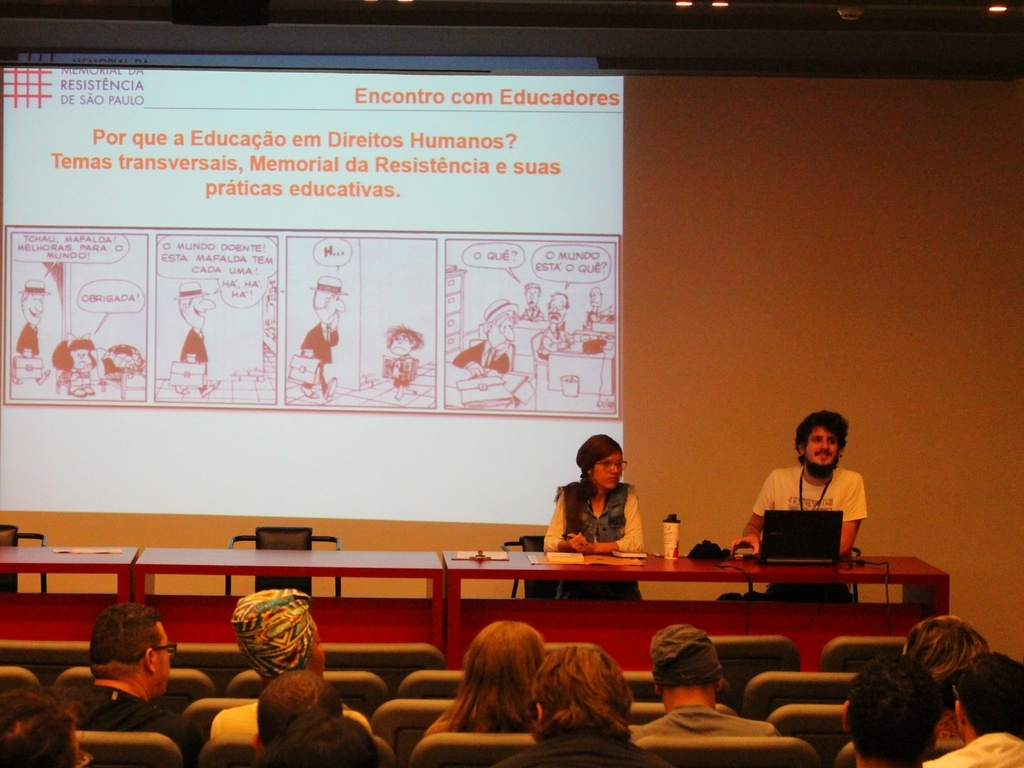 Fotografia de um homem e uma mulher em uma mesa com um notebook na frente do rapaz. Eles estão em um auditório com pessoas observando uma apresentação projetada na parede de uma tirinha da personagem Mafalda.
