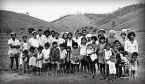 Foto em preto e branco de vários indígenas, que posam em fileiras para a foto. A fileira da frente conta apenas com crianças, de diversas alturas, e ao fundo temos uma outra fileira com adultos. Eles posam em em meio a uma paisagem com montanhas ao fundo.