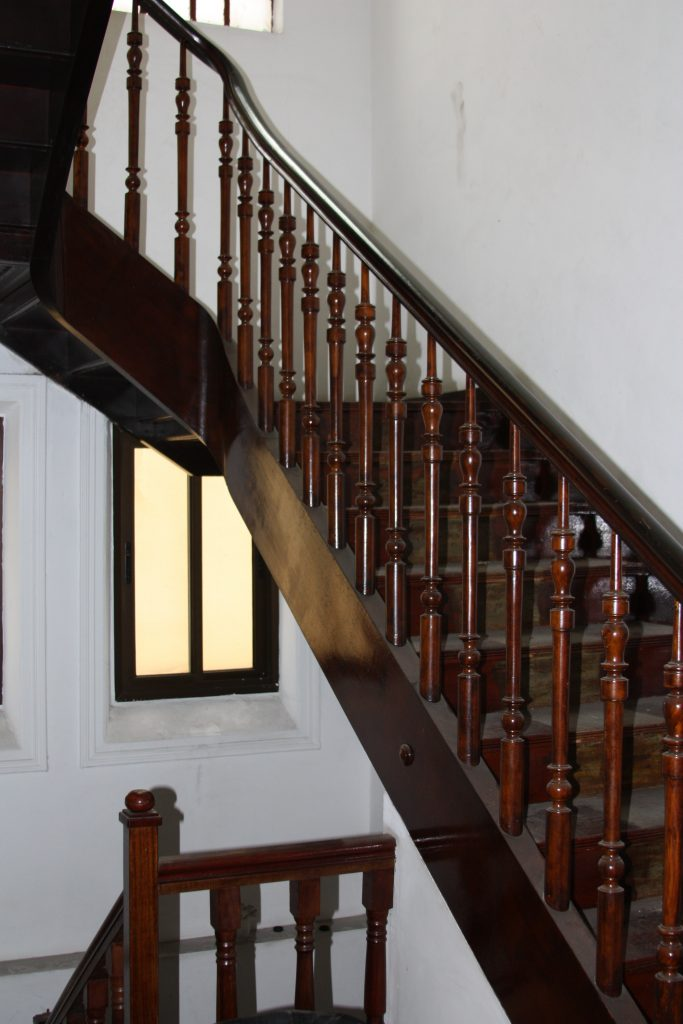 Foto colorida de detalhe da escadaria de madeira escura de um casarão. As paredes no entorno são brancas e os corrimãos são sustentados por um gradeado de madeira trabalhada com motivos que se assemelham a peças do peão do xadrez.
