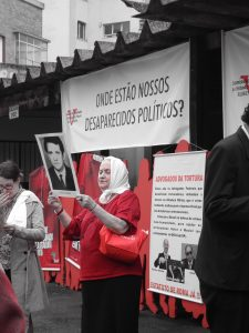 """Foto colorida de mulher de uns 60 anos vestida com uma camisa vermelha e um lenço branco na cabeça segurando uma foto em preto e branco do rosto de um homem que veste terno. Atrás dela há uma faixa branca, que podemos ler com letras pretas os dizeres """"Onde estão nossos desaparecidos políticos?""""."""