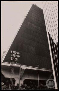 """Foto em preto e branco de um prédio formato de ponta de trapézio isosceles bem alto. Ele está sustentado por largas colunas de concreto. Na sua lateral não há janelas, mas podemos ver que existem entradas de ar e luz por um material parecido com uma grande persiana de metal fixa. Na ponta inferior do trapézio lemos na fachada, com letras grandes """"FIESP, CIESP, SESI"""". No canto esquerdo aparece parte de um outro prédio espelhado."""