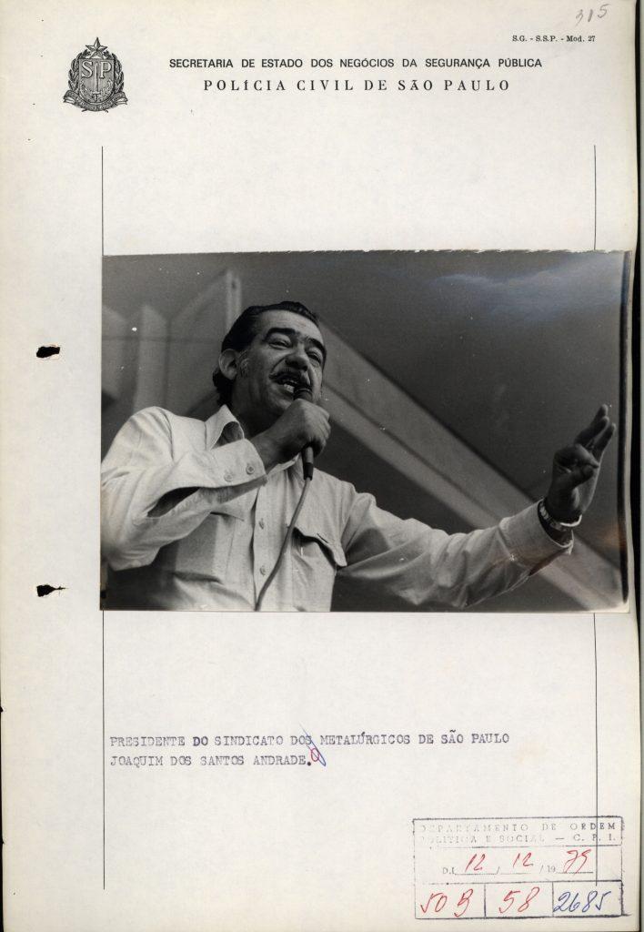 : Foto em preto e branco de homem falando ao microfone. Ele usa uma camisa de manga longa e bigode. A mão direita seguira o microfone e mão esquerda faz um sinal com a junção do polegar com o dedo indicador.