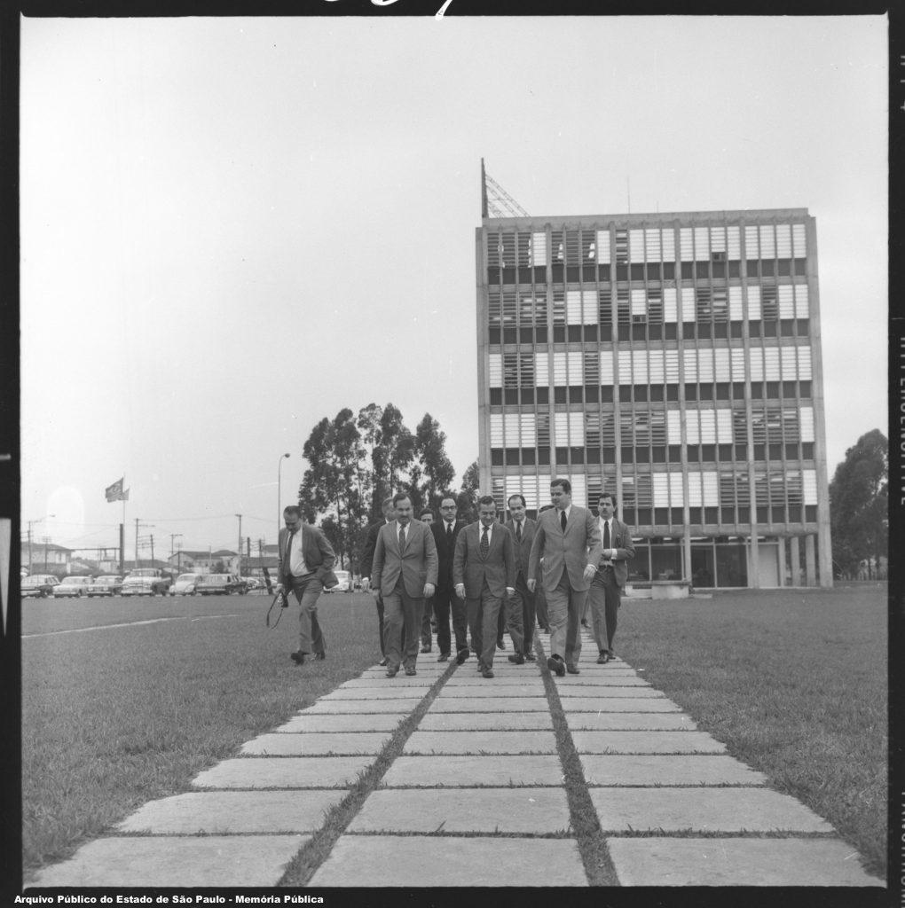 Foto em preto e branco. Dez homens de terno e gravata andam em frente por um caminho de cimento num gramado. Ao fundo há um prédio de escritório de seis