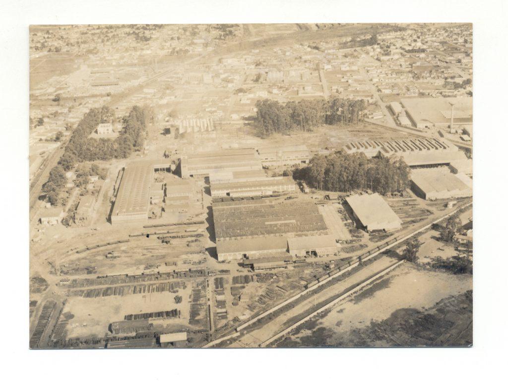 Fotografia aérea em preto e branco de terreno de fábrica. Muito amarelada pelo tempo. Retrata oito galpões, o pátio de trens, as ruas de acesso ao terreno, algumas árvores e, ao fundo, prédios e casas meio borrados pelo tempo.