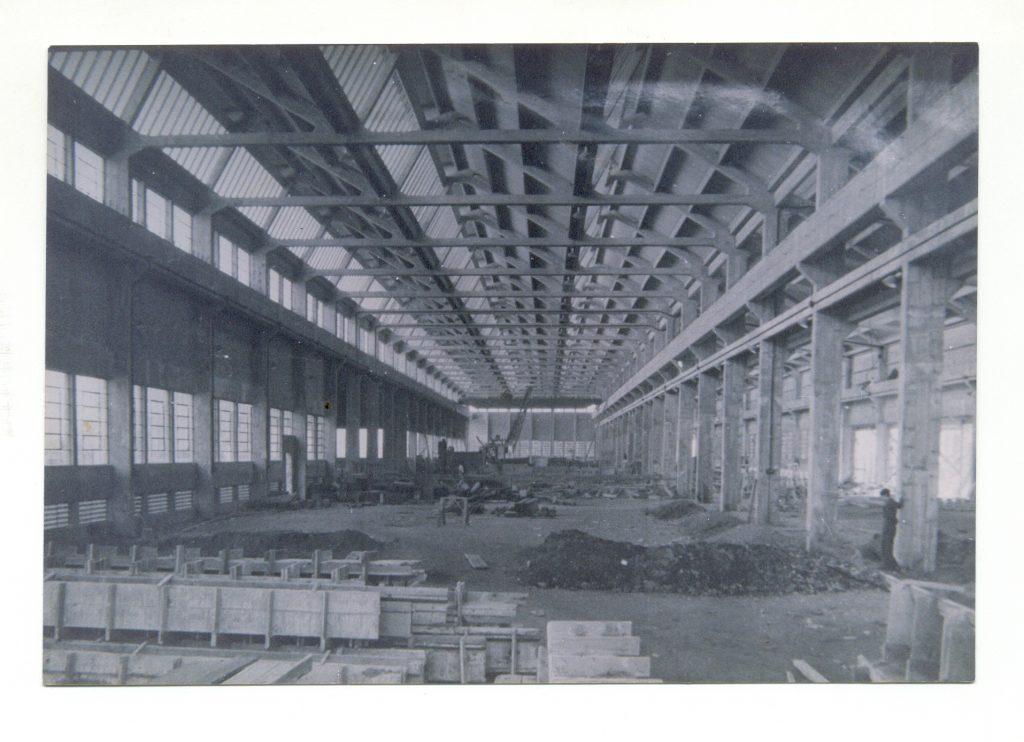 Foto em preto e branco do interior de um galpão em construção. Mostra as vigas de sustentação no teto e nas paredes, janelas do lado esquerdo, alguns homens trabalhando, um monte de terra à frente e estruturas de cimento e madeira.