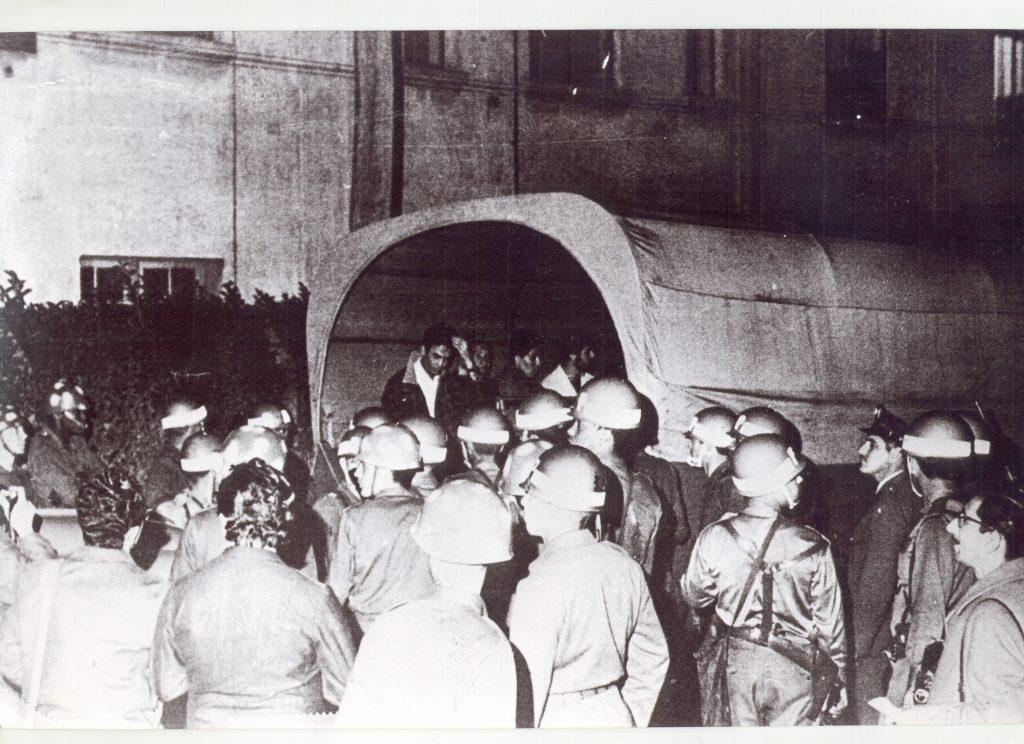 Foto em preto e branco. Muitos policiais de capacete. Ao centro, atrás deles, uma carroça coberta com homens dentro. O primeiro deles está com o braço esquerdo levantado e a mão na cabeça. Ao fundo há um prédio e uma cerca viva.