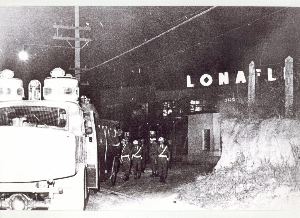: Foto em preto e branco. É noite. À direita e à frente há um camburão da polícia e um poste de iluminação atrás. Ao centro um grupo de policiais fardados.