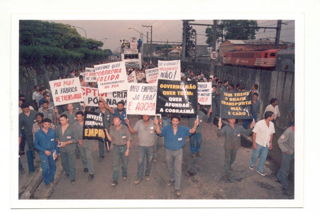 Fotografia colorida. Retrata vários homens segurando cartazes contra o fechamento da Cobrasma num ângulo de frente. Ao lado direito deles há um muro e, atrás dele, um trem e um galpão. Ao fundo um caminhão leva mais homens com cartazes.
