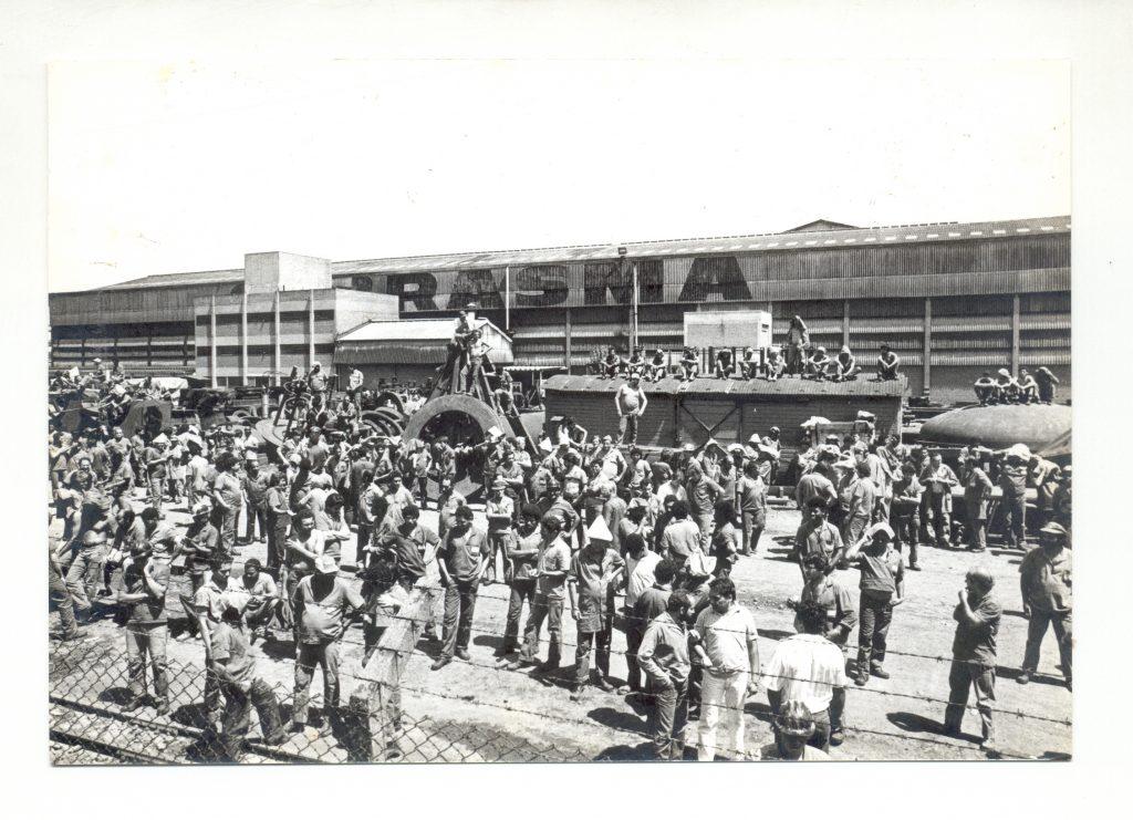 Foto em preto e branco. Muitos homens parados em frente a um galpão. Um trem à direita e homens sentados no teto. No galpão, acima, pode-se ler RASMA, o início da palavra é escondido por um prédio. À frente, parte de uma cerca de ferro com arame farpado