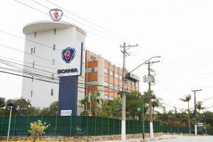 """Foto colorida de um prédio branco com um logo de águia vermelha coroada dentro de um círculo azul no teto. Ao lado, continuação do prédio com tijolos à vista. À frente uma grande placa com o logo onde lê-se """"Scania"""" abaixo. Um portão verde e postes de luz em frente."""