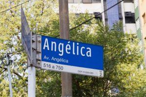 Foto colorida com detalhe da placa de rua azul com uma pequena faixa branca abaixo em que lê-se Angélica, com letras maiores brancas e abaixo lê-se Av. Angélica também em branco. Atrás da placa é possível ver um poste e folhas de árvore.