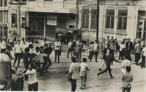 Foto em preto e branco de vários homens jovens espalhados de forma desordenada em uma rua. A maioria está na calçada e apenas observa. No meio da rua há um grupo de 5 homens que carrega um que parece estar desmaiado. Dois outros homens se afastam correndo em direção à calçada. No entorno desta cena, mais homens que observam este movimento.