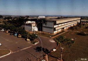 Foto colorida vista de cima. No centro, um prédio branco e cinza de dois andares. Ao fundo e acima há um pouco de morros ao longe e céu azul. Abaixo, um estacionamento com 7 carros e um gramado com árvores.