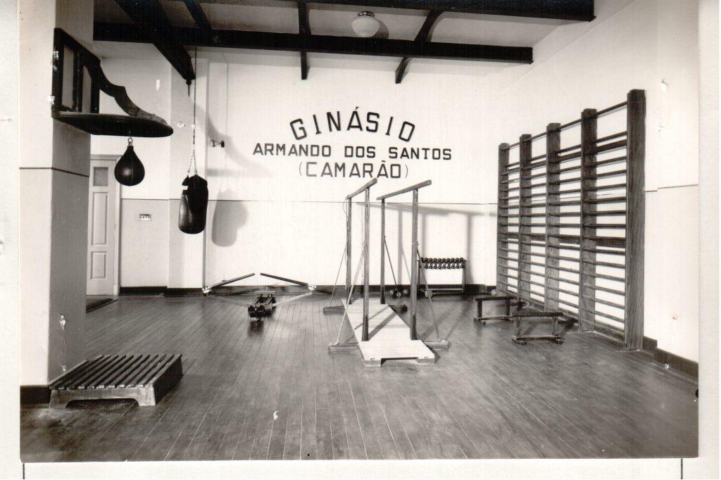 Foto em preto e branco de um ginásio de esportes com 2 barras paralelas no centro, um saco de box ao fundo, um saco de pancada no canto esquerdo e quatro espaldares no canto direito. No Fundo, escrito na parede lemos: Ginásio Armando dos Santos (Camarão).