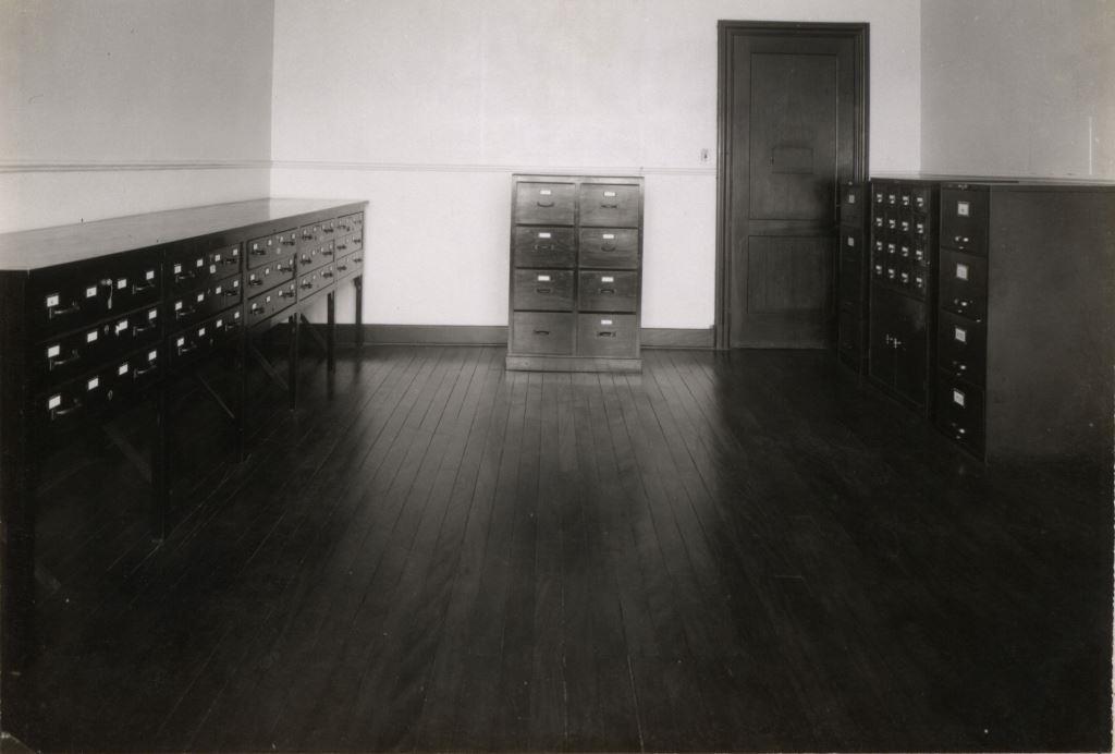 Foto em preto e branco de sala com chão de tábua corrida e gaveteiros, No canto direito 3 gaveteiros de arquivo e uma porta de madeira. Na parede da frente um gaveteiro com 8 gavetas largas de arquivo. E no canto esquerdo um gaveteiros de arquivo com gavetas menores.