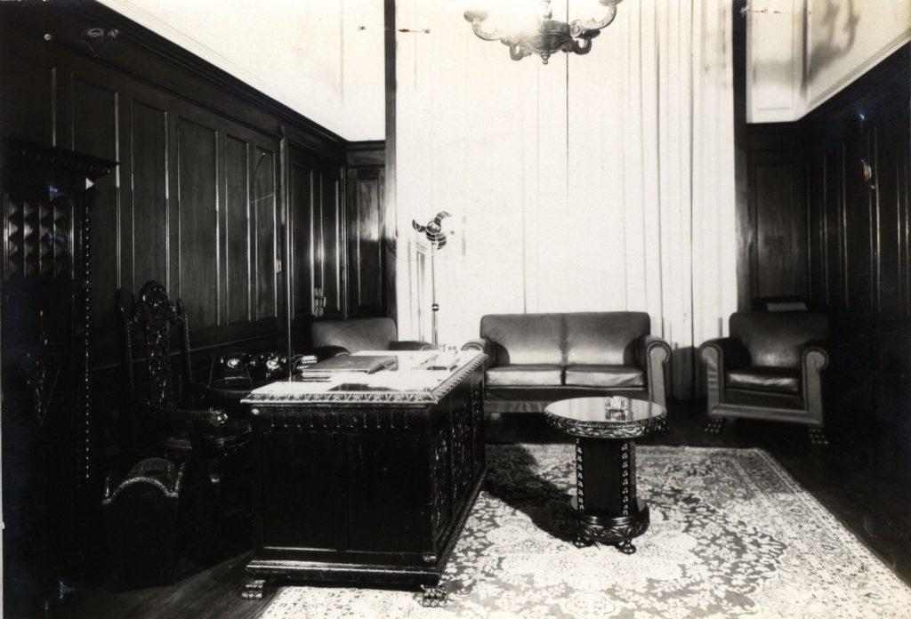 Foto de um escritório com móveis antigos e escuros em cima de um tapete persa. As paredes tem placas de madeira escura. Na lateral esquerda vemos uma mesa de escritório robusta e retangular com entalhes e uma cadeira também com entalhes. No fundo da sala, na frente de cortinas, um sofá de 2 lugares e duas poltronas nas suas laterais. No centro da foto vemos uma mesa de centro redonda e no canto superior vemos parte de um lustre.