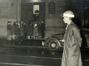 """Foto em preto e branco de uma fila com homens e mulheres aguardando para entrar em uma porta. Na lateral direita da porta vemos uma placa de metal que lê-se """"Quinta Divisão Policial DOPS"""". No canto direito da imagem, atrás de um policial fardado e de capacete, vemos um fusca de cor escura estacionado."""