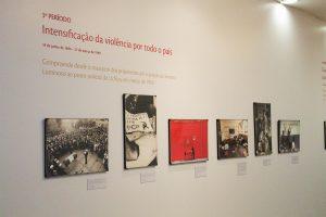 """Foto de uma parede cinza clara com 6 quadros fotográficos (3 deles em preto e branco e 3 coloridos). Acima dos quadros lemos """"3º Período - Intensificação da violência por todo o país""""."""