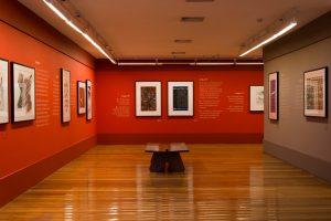 Foto de espaço expositivo com paredes paralelas. A parede da esquerda é vermelha e vemos 5 quadros fotográficos coloridos e em preto e branco. A parede da direita é cinza claro e vemos dois quadros. A parede do fundo é vermelha e possui 3 quadros, um colorido e outro preto. Entre as duas paredes paralelas no centro encontra-se um banco de madeira.