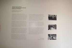 """Foto de parede branca com 3 fotos em preto e branco plotadas de pessoas reunidas, no canto direito. Ocupando o centro e o canto esquerdo vemos um texto cujo o título diz: """" Artistas nipo-brasileiros durante a Segunda Guerra Mundial: Esperança nos trópicos""""."""