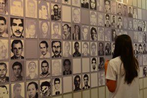 Foto colorida de garota que observa muitas fotos 3x4 de homens e mulheres em preto e branco, formando um quadriculado. Neste quadriculado, por entre as fotos, aparecem alguns espaços vazios.
