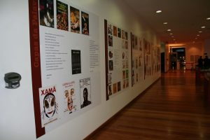 Foto colorida de área expositiva com parede branca com vários cartazes e piso de madeira. As obras estão dispostas num quadrado cujo centro contém escritos.