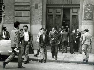 """Foto em preto e branco de homens saindo para rua por uma larga porta de 4 divisões, onde apenas uma está aberta. Na lateral direita da porta, em uma parede de tijolos a vista, vemos uma placa de metal que lê-se """"Quinta Divisão Policial DOPS""""."""