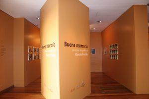 """Foto colorida de parte de um espaço expositivo. Vemos paredes beges na lateral com 9 quadros pendurados do lado direito e 6 quadros do lado esquerdo. No centro uma larga coluna em forma de losango onde lemos em seu centro os escritos: """"Buena Memória: um ensaio fotográfico de Marcelo Brodsky"""""""