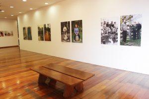 Foto do espaço expositivo com paredes brancas e chão de madeira. No primeiro plano da foto encontra-se um banco marrom comprido e plano e nas paredes brancas quadros fotográficos coloridos e preto e branco.