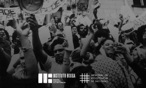 """Foto preto e branco de homens e mulheres em um grupo se manifestando. Muitos seguram papéis nas mãos estendidas para cima. Em um dos papéis lemos """"Viver é um direito do povo"""". Algumas pessoas seguram panelas também para cima. Ao fundo vemos uma faixa. No canto inferior vemos as logomarcas do Instituto Bixiga e do Memorial da Resistência"""