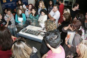 Foto colorida de pessoas reunidas no entorno de uma maquete de espaço carcerário. Algumas observam a maquete enquanto outras prestam atenção em uma educadora que fala gesticulando.