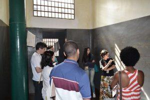 Foto de um grupo de pessoas dentro de uma cela olhando para uma educadora que aponta para uma parede cinza cheia de rasuras.