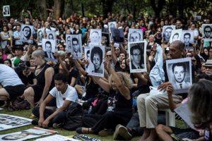 Foto colorida de pessoas reunidas em uma manifestação pacífica. Algumas delas seguram em frente ao corpo fotografias em preto e branco de desaparecidos e mortos políticos
