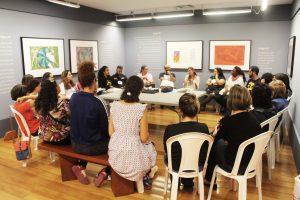 Foto de pessoas sentadas em cadeiras dispostas em um círculo em um espaço expositivo com quadros coloridos. Todos olham para uma mulher de óculos que está falando.