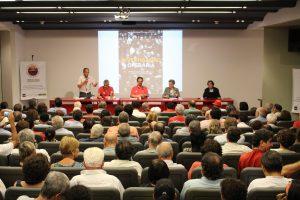 Foto colorida de pessoas em um auditório. Seis delas estão apresentando atrás de uma mesa comprida vermelha, enquanto as demais assistem. Na parede, atrás da mesa vermelha, há uma projeção na parede