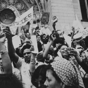 """Foto preto e branco de homens e mulheres em um grupo se manifestando. Muitos seguram papéis nas mãos estendidas para cima. Em um dos papéis lemos """"Viver é um direito do povo"""". Algumas pessoas seguram panelas também para cima."""