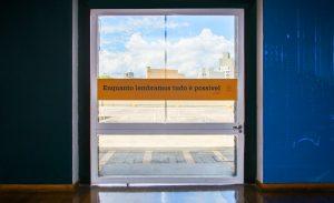 """Foto colorida do espaço interno do Memorial da Resistência. Na imagem aparece, ao centro, uma porta de vidro, onde se vê ao fundo um estacionamento, alguns prédios no horizonte e o céu com nuvens. Colado na porta de vidro, uma faixa laranja tem escrita em preto a frase """"Enquanto lembrarmos tudo é possível""""."""