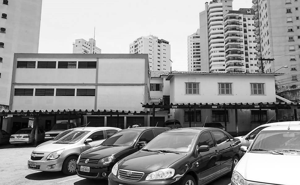 Foto em preto e branco de pátio de estacionamento com 10 carros estacionados. Na frente da imagem, 4 deles estão parados em um ângulo de 45º enquanto os demais estão estacionados debaixo de uma área coberta. Ligado a esta área uma construção larga de 3 andares com 8 janelas retangulares do lado esquerdo e 6 janelas quadradas do lado direito. Ao fundo prédios de apartamentos altos.