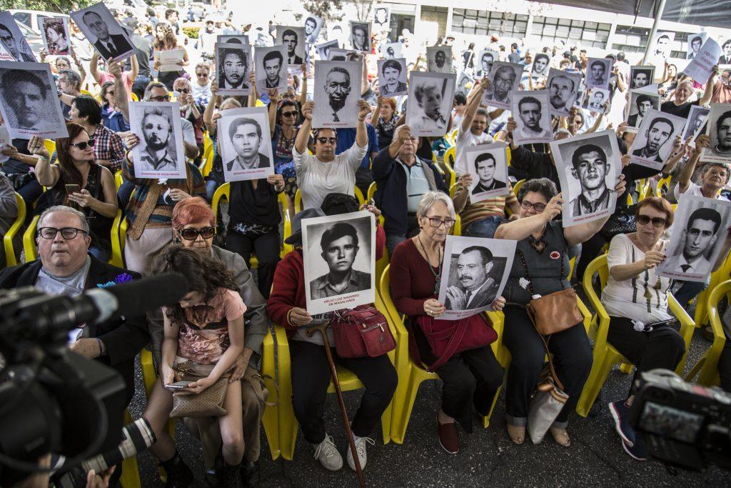 Foto colorida de várias pessoas sentadas em cadeiras amarelas segurando fotografias em preto e branco do tamanho A3 de rostos. Muitas delas colocaram a fotografia em frente ao próprio rosto, enquanto outras seguram a imagem acima da própria cabeça.