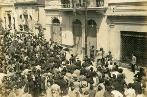 Foto em preto e branco de uma grande multidão de homens tentando invadir um prédio. Na parte central da imagem vemos que parte deste grupo segura uma barra de ferro que está sendo pressionada sobre a porta de um edifício.