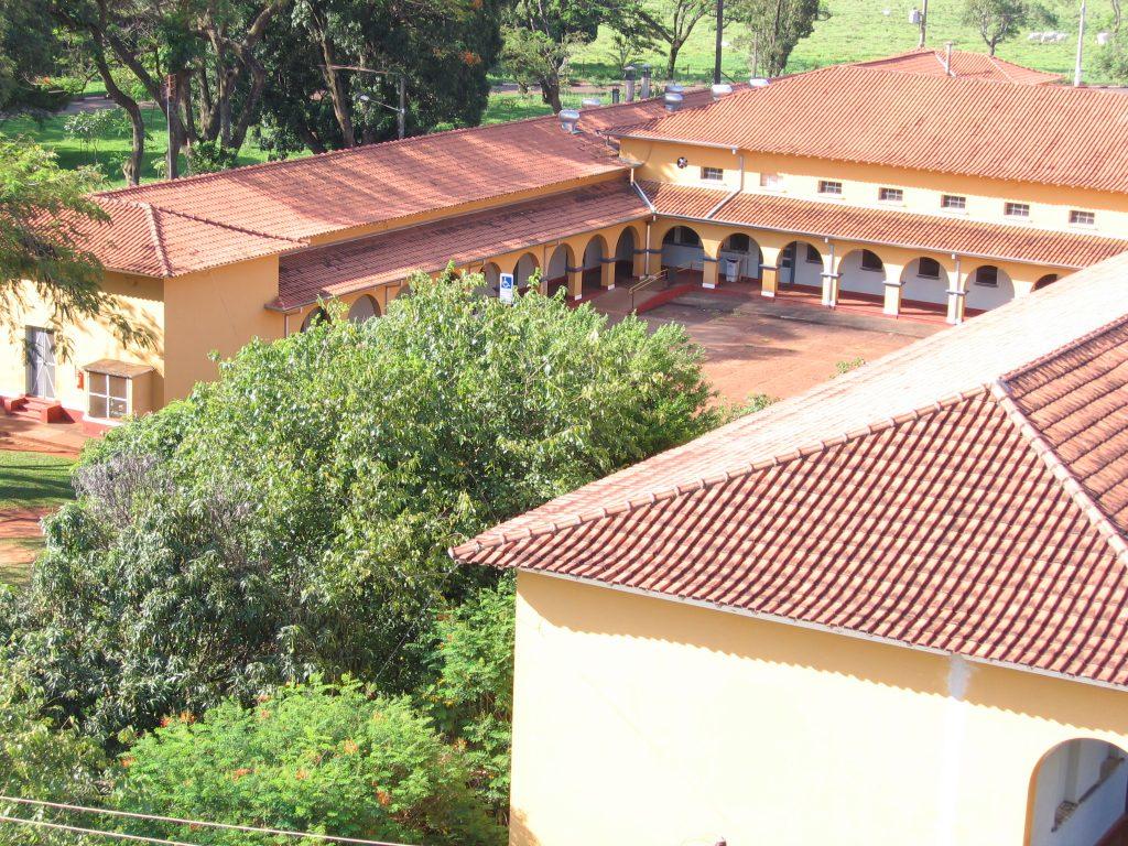 : Foto colorida pátio central de uma construção de 2 andares. O piso inferior apresenta varanda com arcos redondos. No angula da imagem vemos os telhados da construção, feitos de alvenaria. As paredes são amarelas.