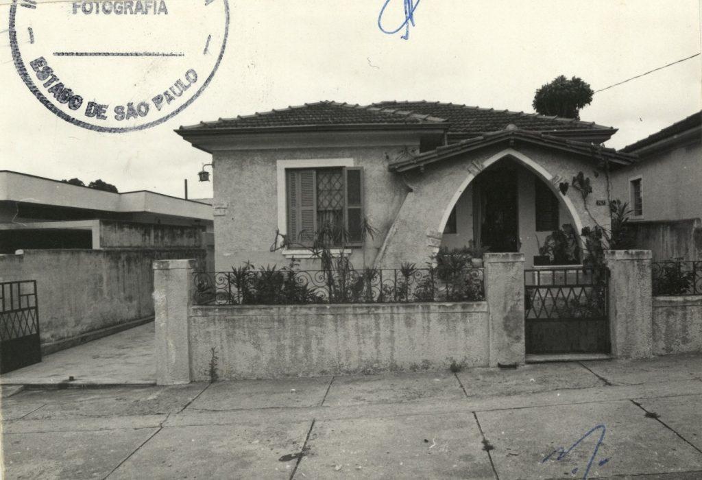 Fotografia em preto e branco que mostra a fachada da Casa da Lapa. Vemos uma mureta que revela seu pequeno jardim. Atrás, uma casa simples com varanda cujo acesso se da por um arco ogival do lado direito. Do lado esquerdo vemos uma janela quadrada.